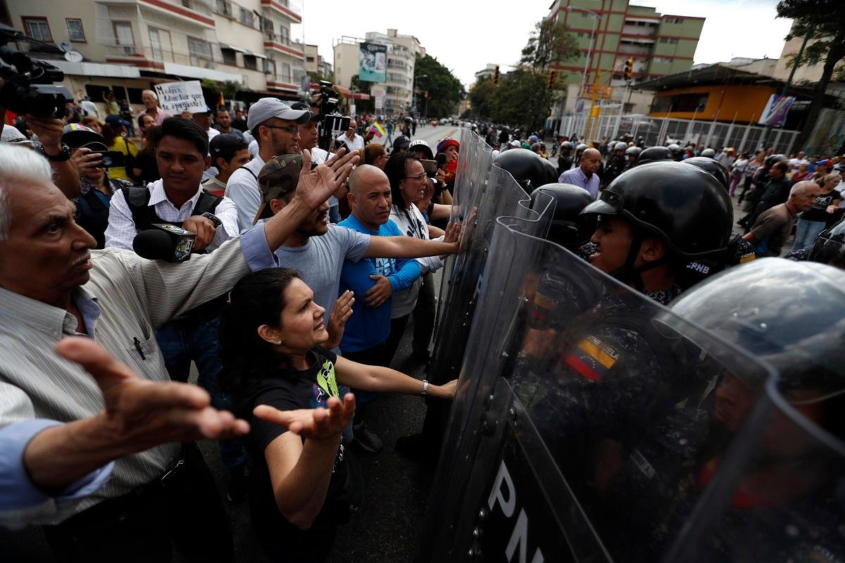 Venezuelan police block a crowd of people who gather to march against the government of President Nicolas Maduro. (AP Photo/Eduardo Verdugo)