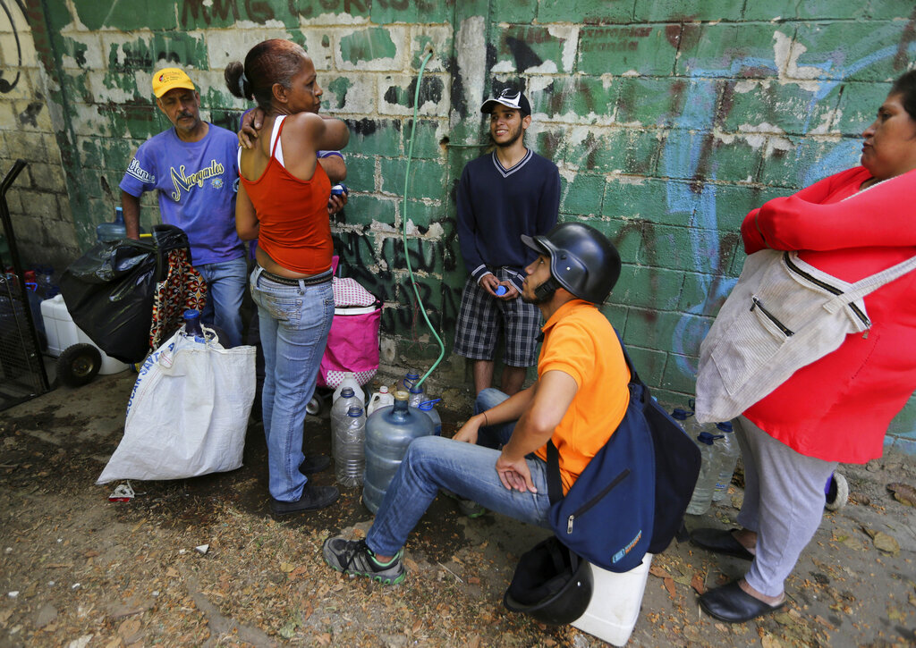 People chat as they fill containers with water from a public fountain, in Caracas, Venezuela, Tuesday, March 12, 2019. (AP Photo/Fernando Llano)