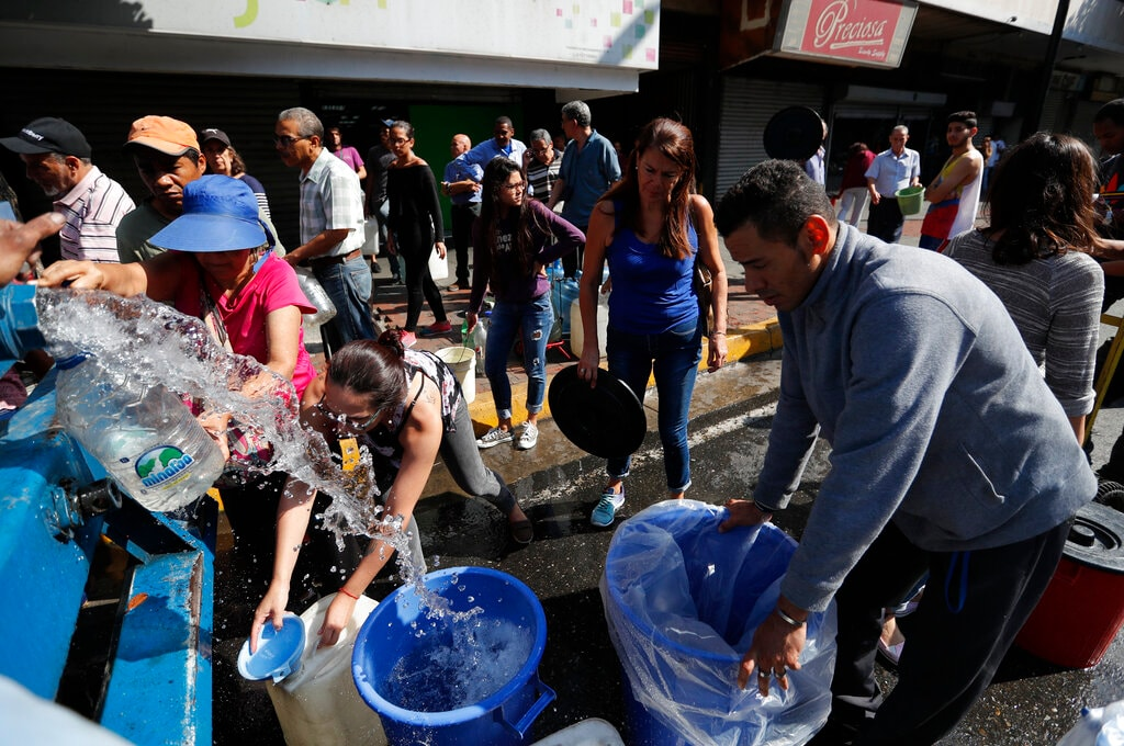 People collect water from a truck that delivers water during rolling blackouts, in Caracas, Venezuela, Tuesday, March 12, 2019. (AP Photo/Eduardo Verdugo)