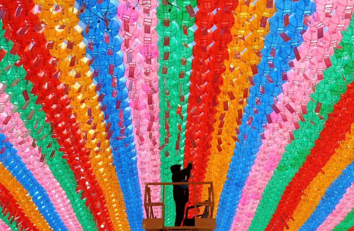 A worker attaches a name tag of a Buddhist who made the donation to a lantern for the upcoming celebration of Buddha's birthday on May 12 at the Jogye temple in Seoul, South Korea. Similar lanterns will be displayed in all Buddhist temples around South Korea for the public viewing. (AP Photo/Ahn Young-joon)