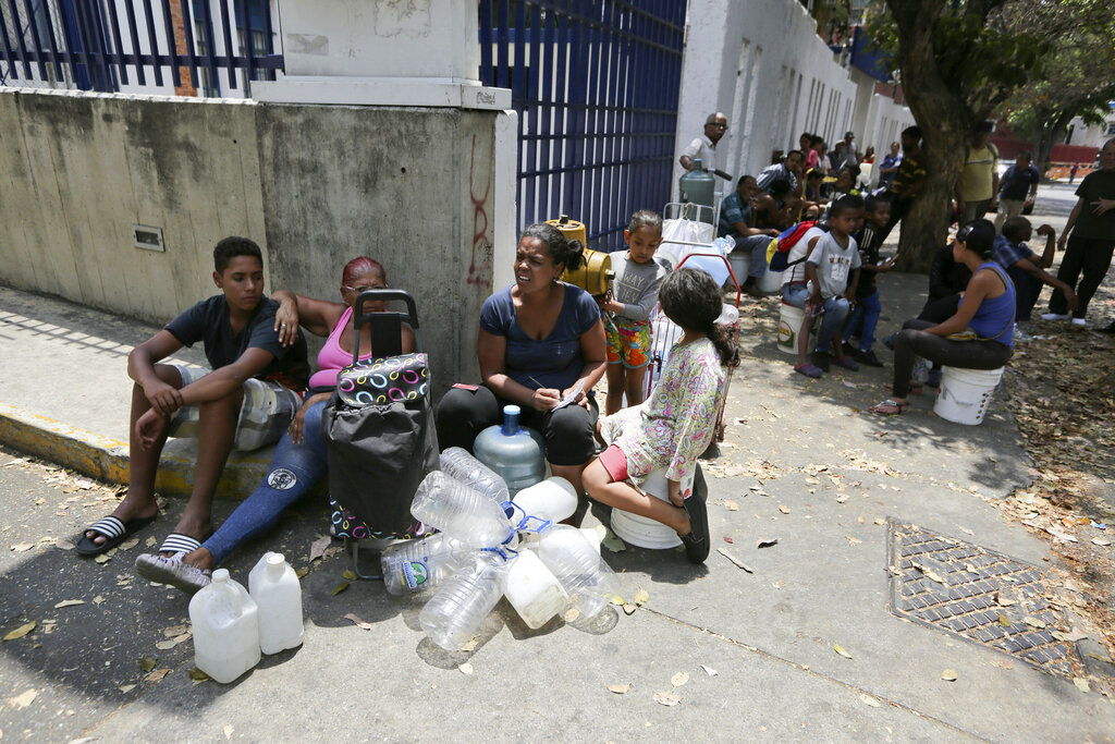 People wait their turn to fill containers with water from a public fountain in Caracas, Venezuela, Wednesday, March 13, 2019. (AP Photo/Fernando Llano)