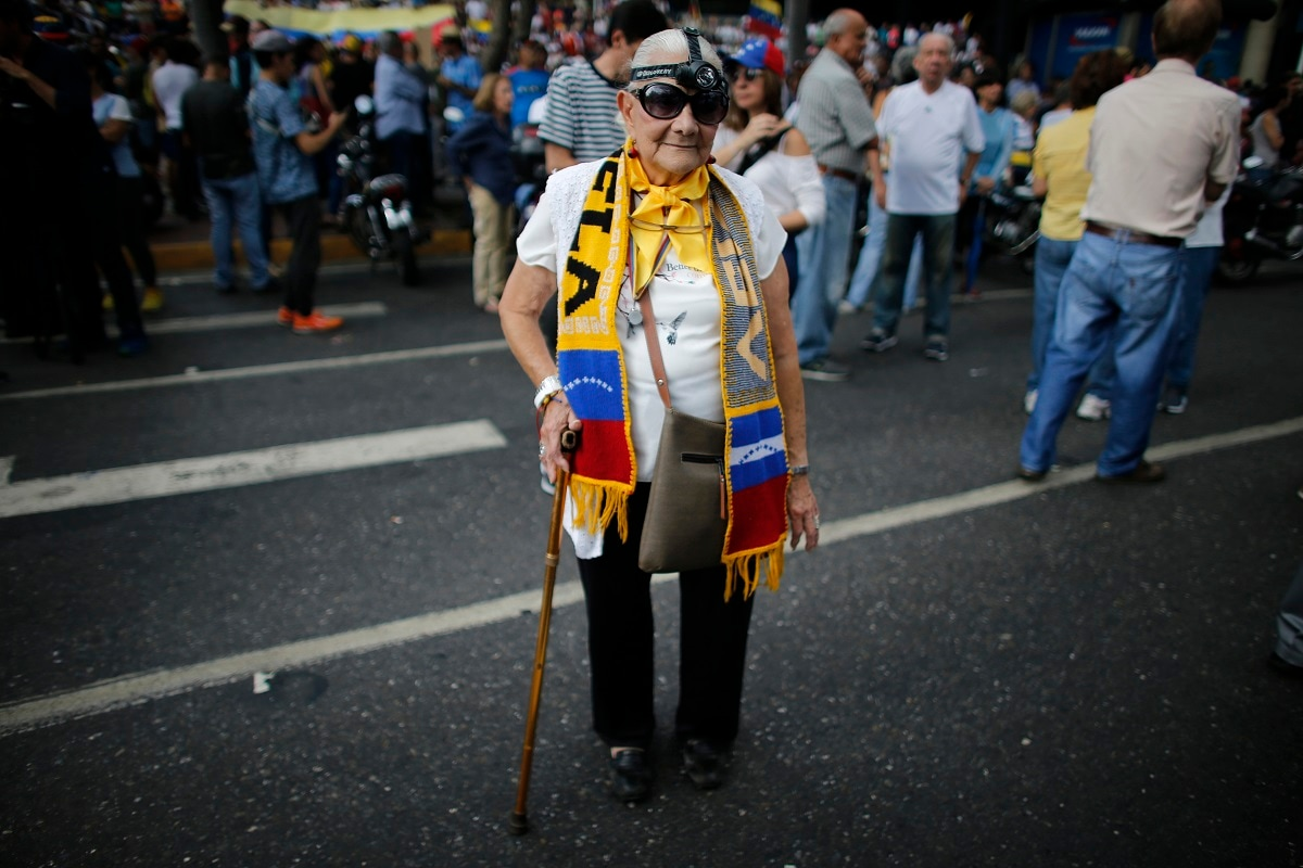 Trina Parry, 83, sporting a headlight headlamp, joins a protest against the government of President Nicolas Maduro, in Caracas, Venezuela. A massive blackout that left millions of Venezuelans without power for four days has triggered one persistent question: How could a country with the world's largest proven oil reserves go dark? (AP Photo/Ariana Cubillos)