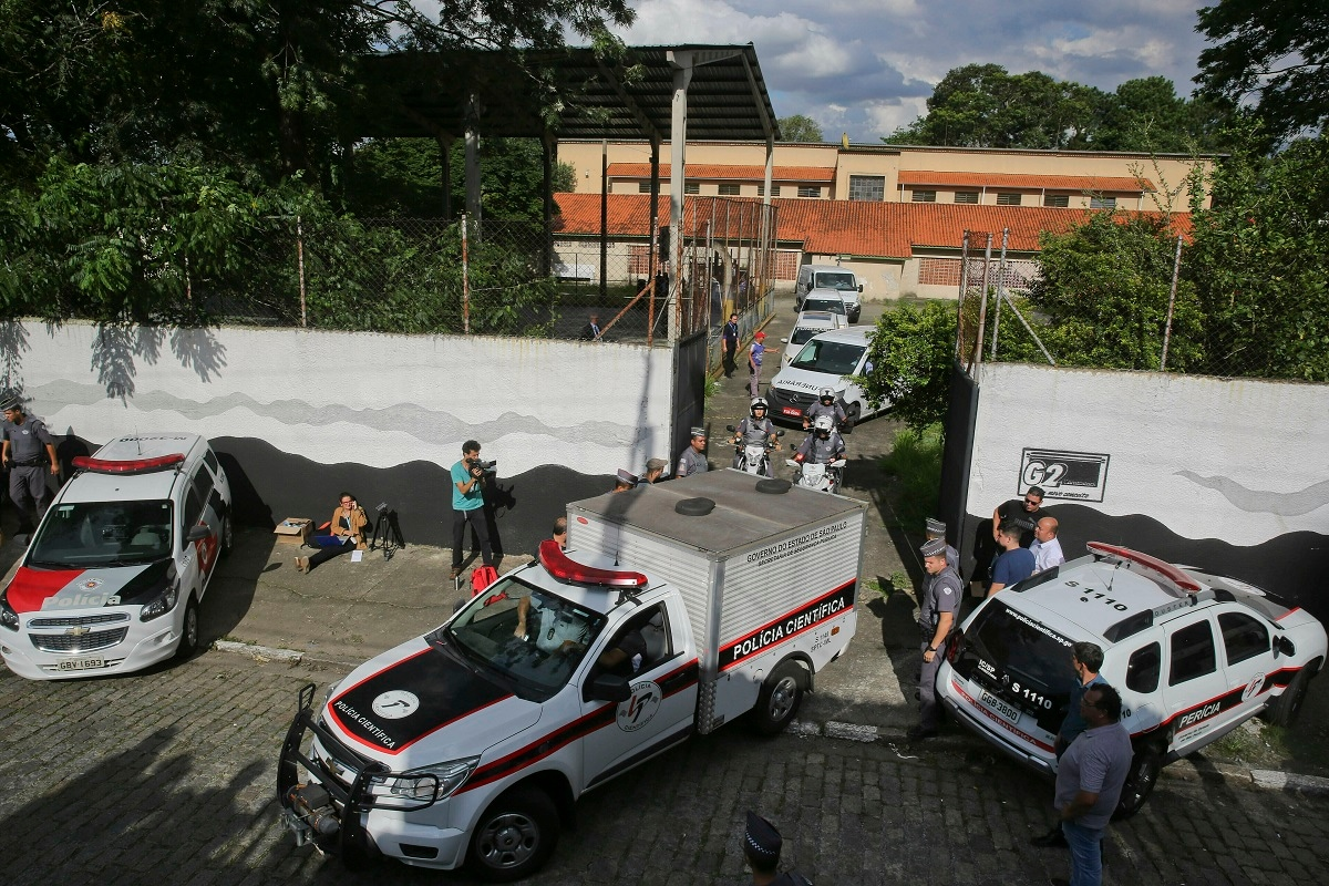 A fleet of funeral vans transport the bodies of the people who were killed in a school shooting at the Raul Brasil State School in Suzano, Brazil. Two masked former students armed with guns, knives, axes and crossbows descended on the school Wednesday, killing five students and two adults before taking their own lives, authorities said. (AP Photo/Andre Penner)