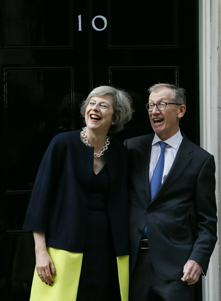 In this Wednesday, July 13, 2016 file photo, British Prime Minister Theresa May and her husband Philip May stand on the steps of 10 Downing Street in London. David Cameron had stepped down Wednesday after six years as prime minister. (AP)