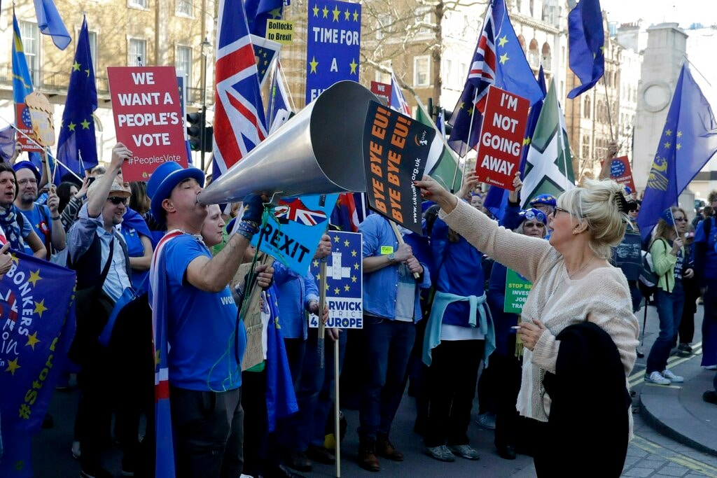 In this Wednesday, Feb. 27, 2019 file photo, a leave the European Union (EU) supporter, at right, holds a placard up in front of remain in the EU supporters protesting outside Downing Street in London. (AP)