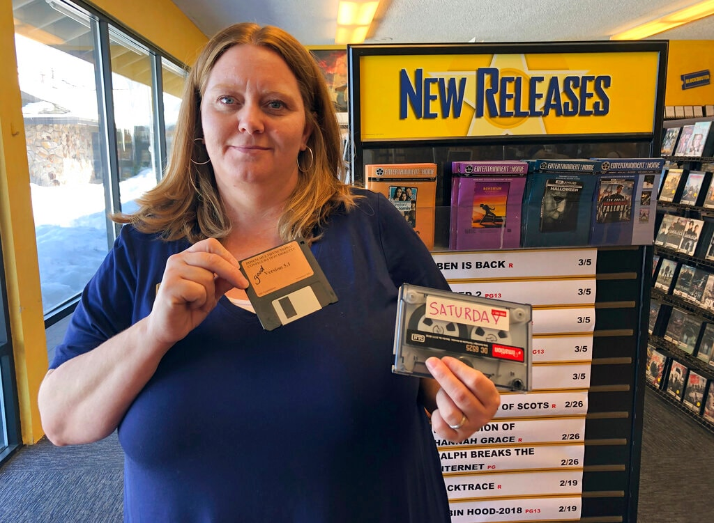 Sandi Harding, general manager of the last Blockbuster on the planet in Bend, Ore., poses for a photo inside the store on Monday, March 11, 2019. Harding is holding up the floppy disc she uses to reboot her computer and the reel-to-reel tape used to back up transactions. (AP)