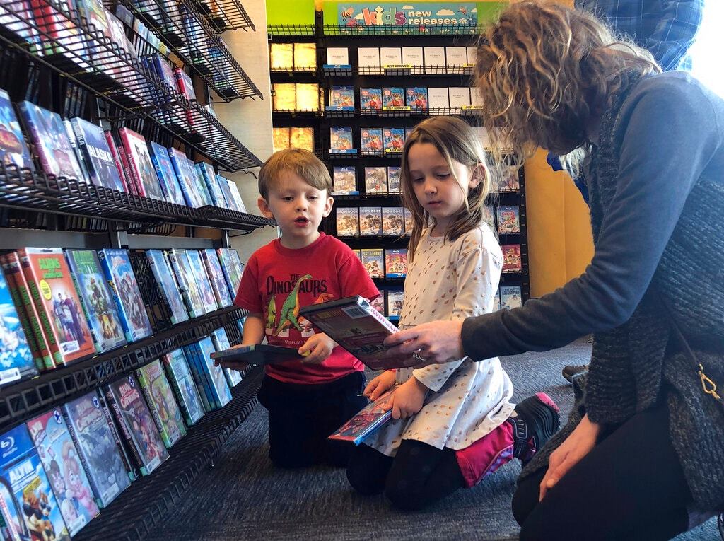 Elizabeth Gilless, of Memphis, Tenn., shows her children John, 3, and Ellen, 5, a movie from the children's section at the last Blockbuster on the planet in Bend, Ore., on Tuesday, March 12, 2019. The family was vacationing in Oregon and stopped by the store to buy souvenirs on their way to Portland, Ore., after hearing it was the last Blockbuster on the planet. (AP)