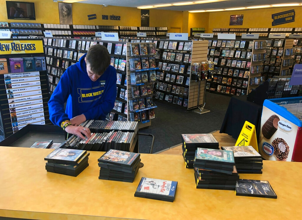 Employee Ryan Larrew alphabetizes returned movies before re-shelving them at the last Blockbuster store on the planet in Bend, Ore., on Tuesday, March 12, 2019. (AP)