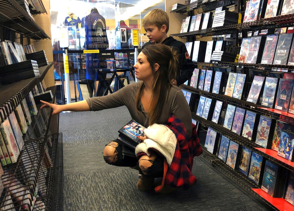 Tia Thiel and her son, Micah Knox, 7, browse a selection of movies at the last Blockbuster on the planet in Bend, Ore., on Monday, March 11, 2019. Thiel is a regular at the store and says she goes to the store for the older movies she can't find on streaming services like Netflix. (AP)