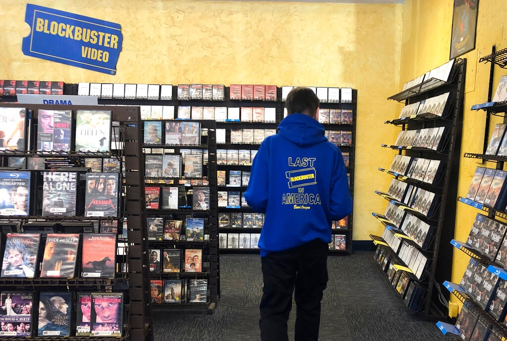 Employee Ryan Larrew reshelves movies that have been returned to the last Blockbuster store on the planet in Bend, Ore., in this Tuesday, March 12, 2019 photo. Larrew's sweatshirt advertises the store as the last one in America, but the store has ordered new sweatshirts and T-shirts saying it is the last Blockbuster on the planet. (AP)