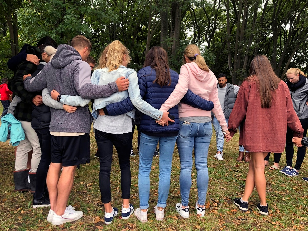 Mourners link arms in Hagley Park near the Al Noor mosque, one of the mosque shooting sites in Christchurch. (AP Photo/Kristen Gelineau)