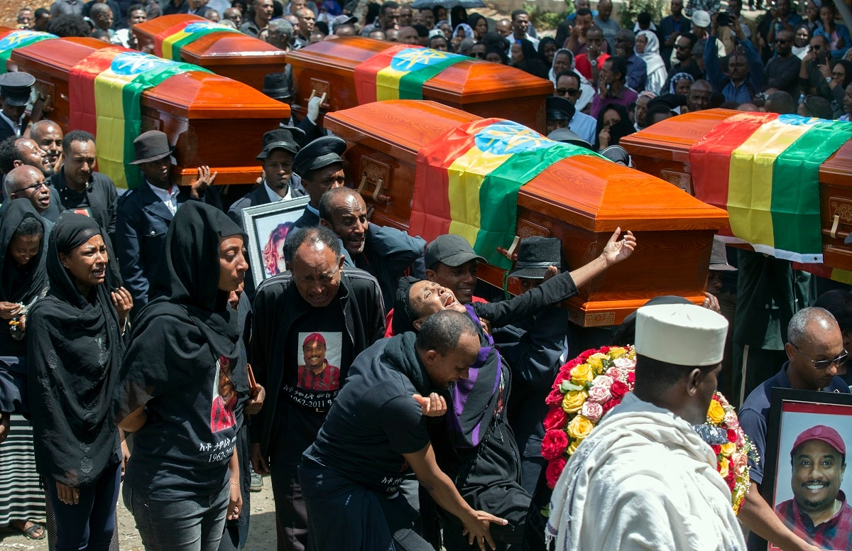 Relatives grieve next to empty caskets draped with the national flag at a mass funeral at the Holy Trinity Cathedral in Addis Ababa, Ethiopia. (AP Photo/Mulugeta Ayene)