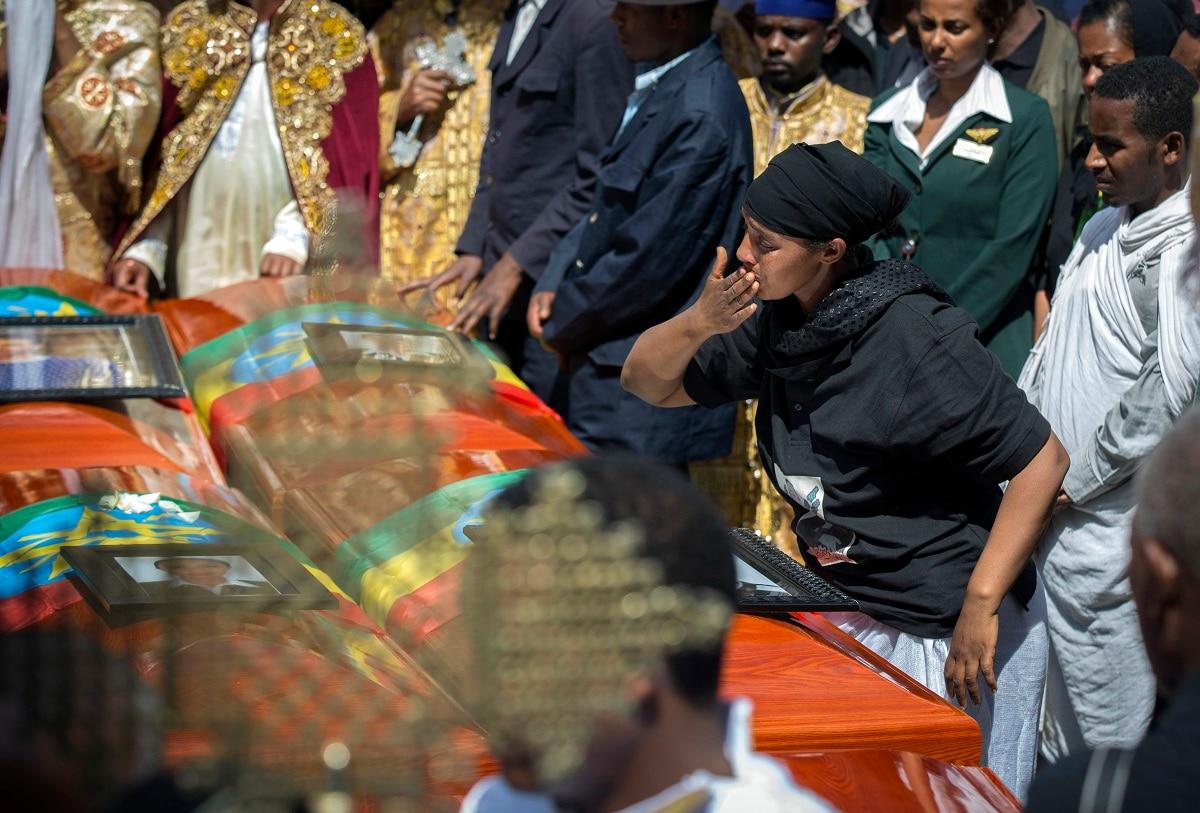 A relative blows a kiss towards empty caskets. (AP Photo/Mulugeta Ayene)