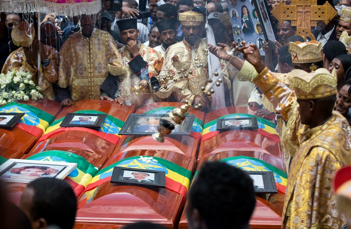 Priests swing incense over empty caskets draped with the national flag. (AP Photo/Mulugeta Ayene)