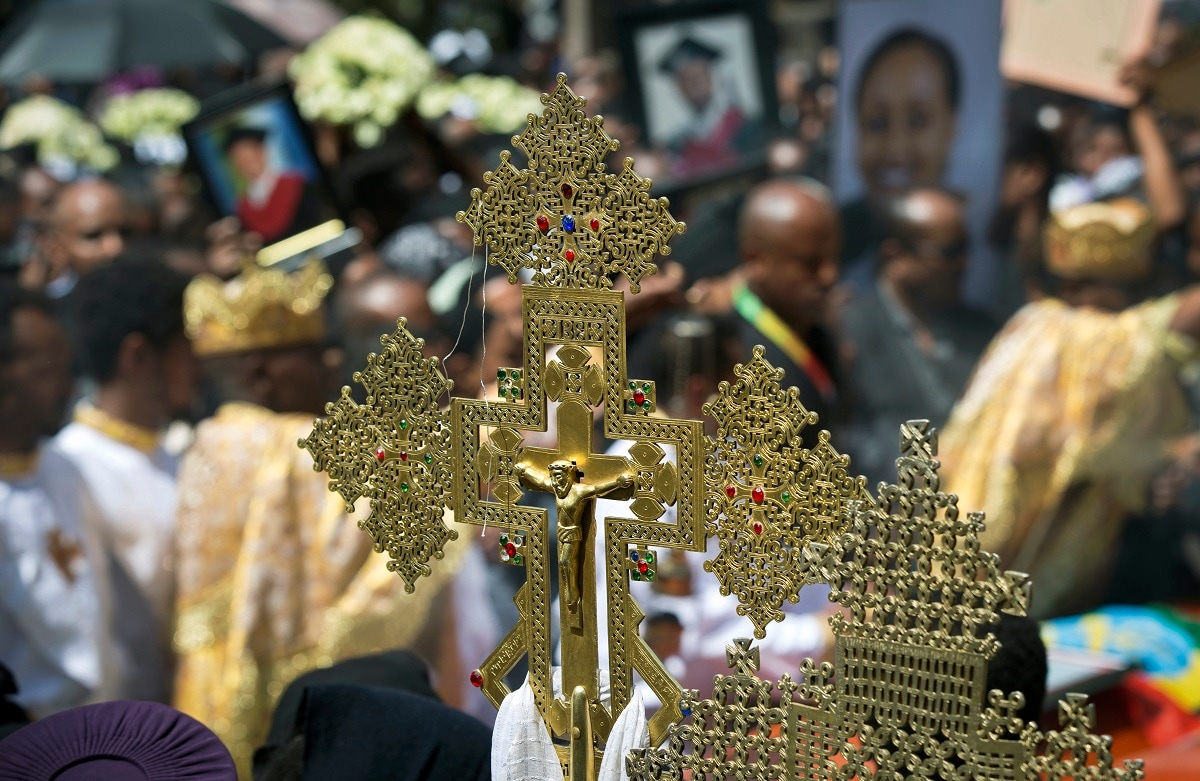 A crucifix is held by a priest at a mass funeral at the Holy Trinity Cathedral. (AP Photo/Mulugeta Ayene)