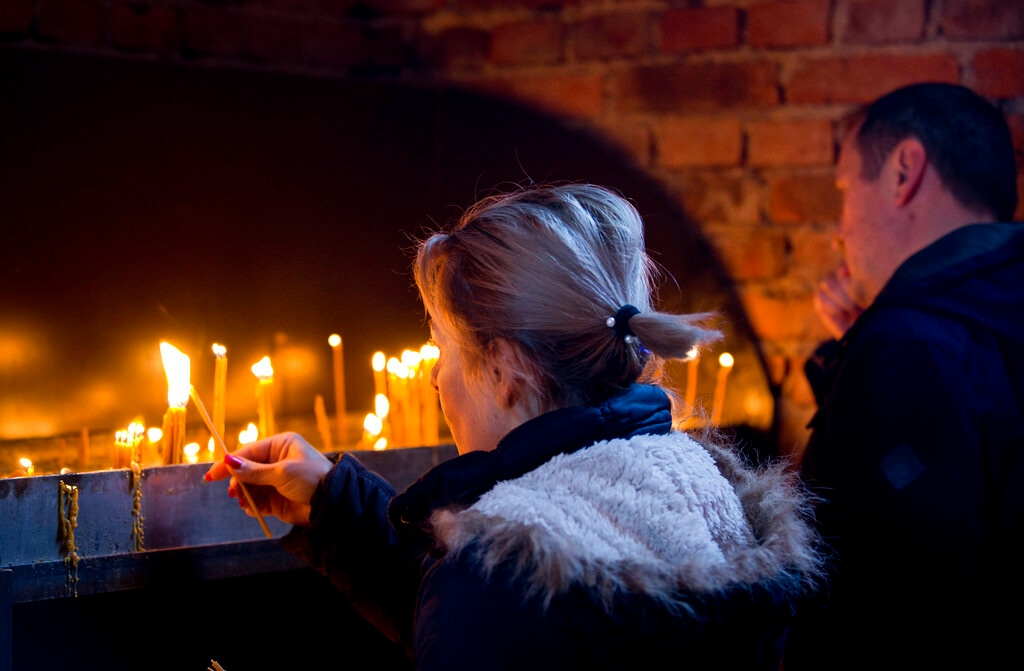 In this Sunday, March 17, 2019 photo, a woman lights a candle at an Orthodox church in the Bosnian Serb wartime stronghold of Pale, Bosnia-Herzegovina.(AP Photo/Darko Bandic)