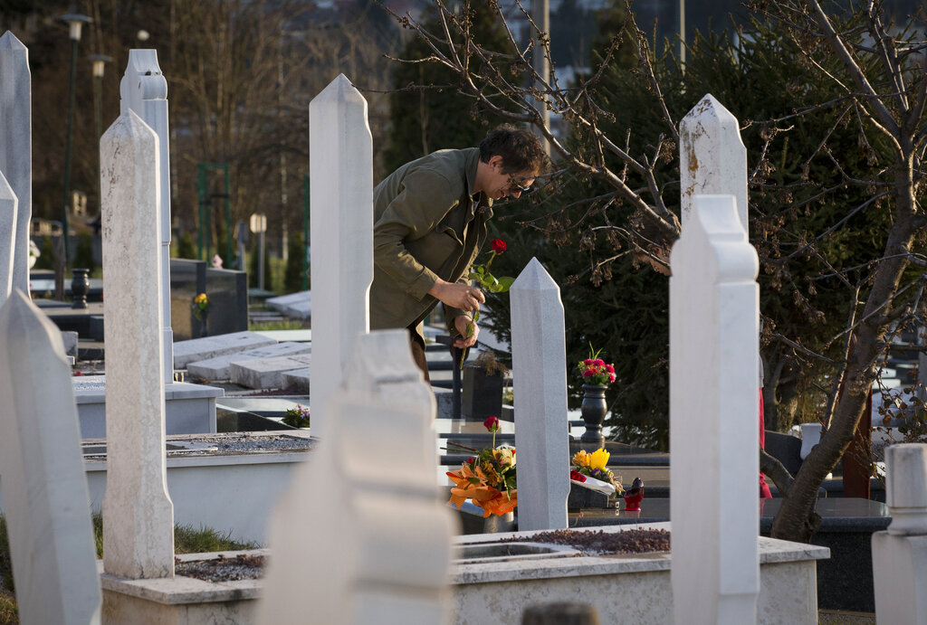 In this Sunday, March 17, 2019 photo, a man places flowers at the section of a cemetery for 1990s war victims in Sarajevo, Bosnia-Herzegovina. (AP Photo/Darko Bandic)