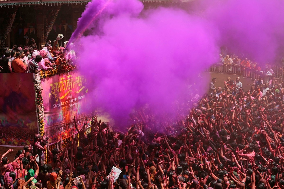 Priests spray coloured water and powder on devotees during celebrations marking Holi at the Swaminarayan temple in Ahmadabad. (AP Photo/Ajit Solanki)