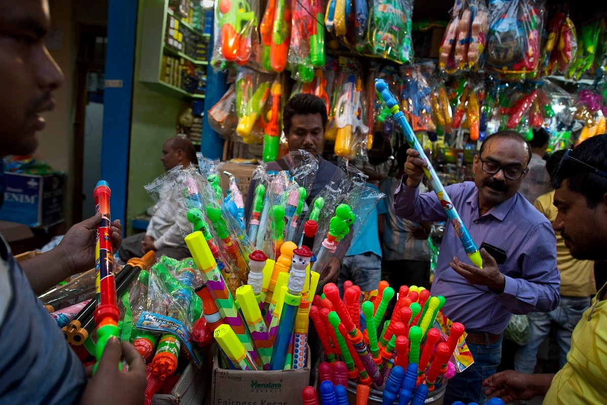 People shop for spray guns a day ahead of Holi in Gauhati. Spray guns are filled with colored water to squirt on fellow revelers during Holi, a festival that also marks the advent of Spring season. (AP Photo/Anupam Nath)