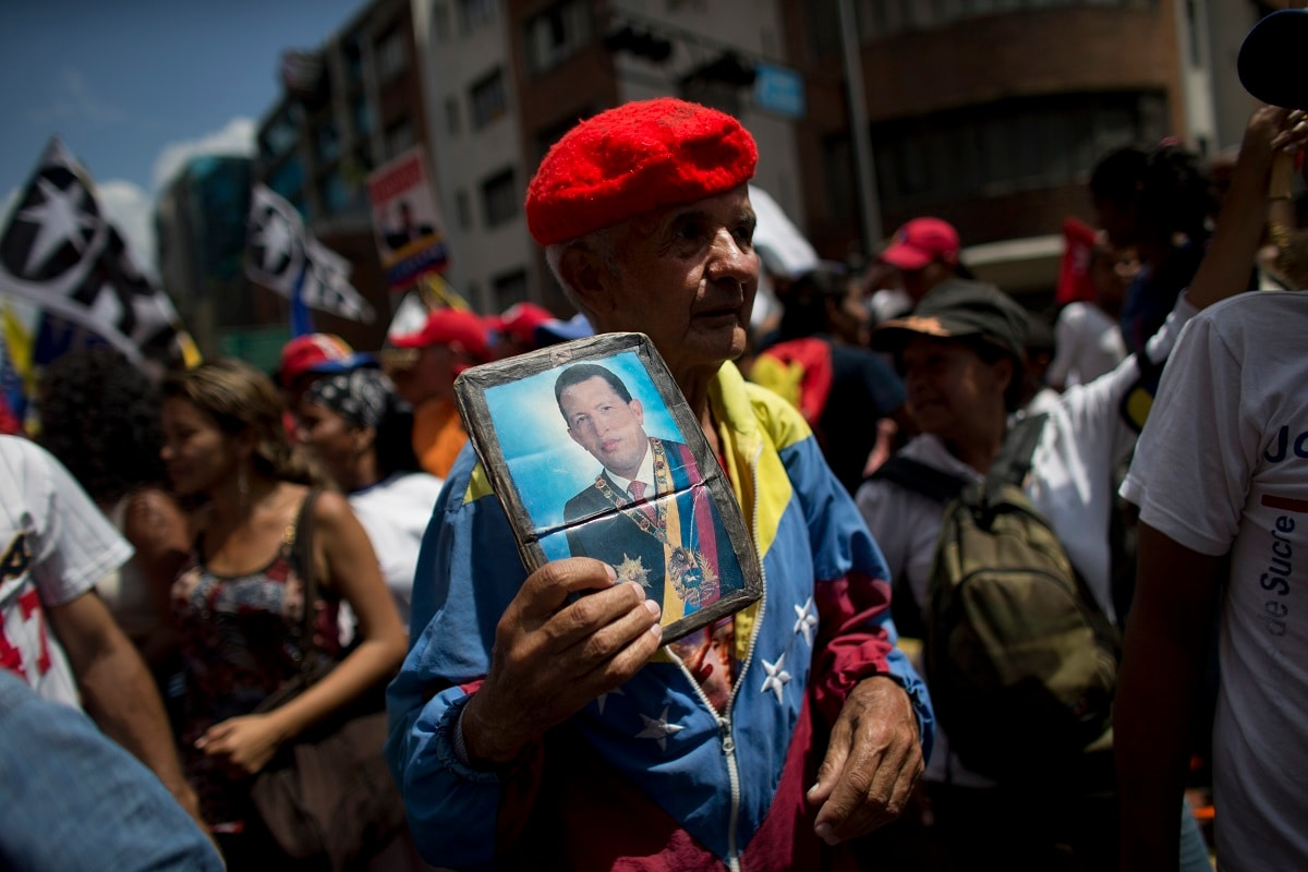 A supporter of Venezuela's President Nicolas Maduro holds a picture of the late President Hugo Chavez during an anti-imperialist march in Caracas, Venezuela. Many were clad in red, the color associated with the movement led by Chavez, the former military officer who declared a socialist