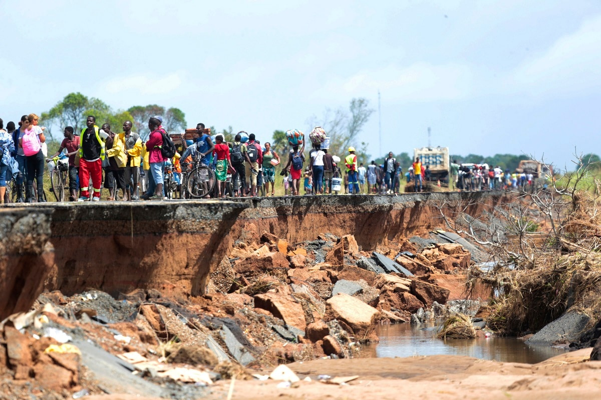 People pass through a section of the road damaged by Cyclone Idai in Nhamatanda about 50 kilometres from Beira, in Mozambique. (AP Photo/Tsvangirayi Mukwazhi)