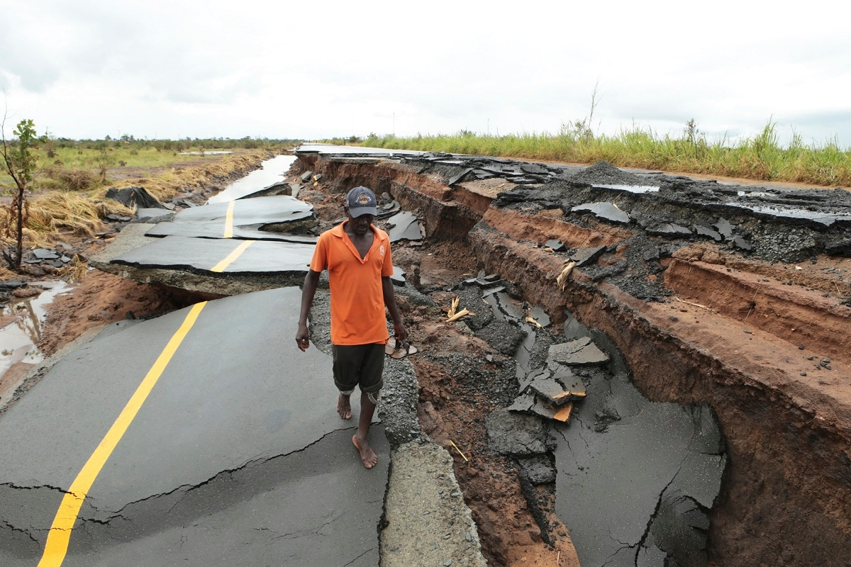 A man passes through a section of the road damaged by Cyclone Idai. (AP Photo/Tsvangirayi Mukwazhi)