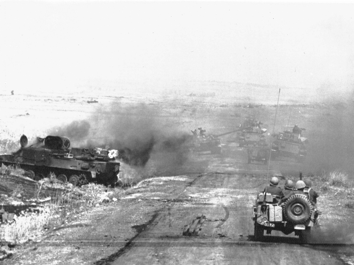 In this October 9, 1967, file photo, an Israeli column passes a burning Syrian tank in the Golan Heights as they head toward the fighting on the Israeli-Syrian front. The Golan Heights is a strategic high ground at the southwestern corner of Syria with stunning broad views of both Israel and Syria below. Israel captured the territory in the 1967 Mideast War and annexed it in 1981, a move that was never recognized by any country in the world. (AP Photo/File)