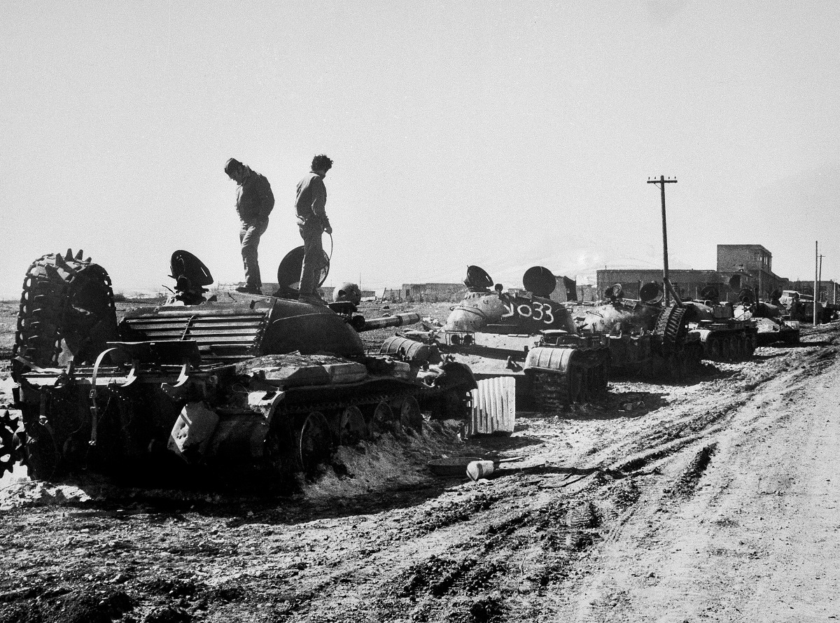 In this October 1973, file photo, Israeli soldiers look at a long row of burned-out Syrian T-62 tanks hit at the entrance of a village, background, during the Mideast War in the Golan Heights.  (AP Photo/File)