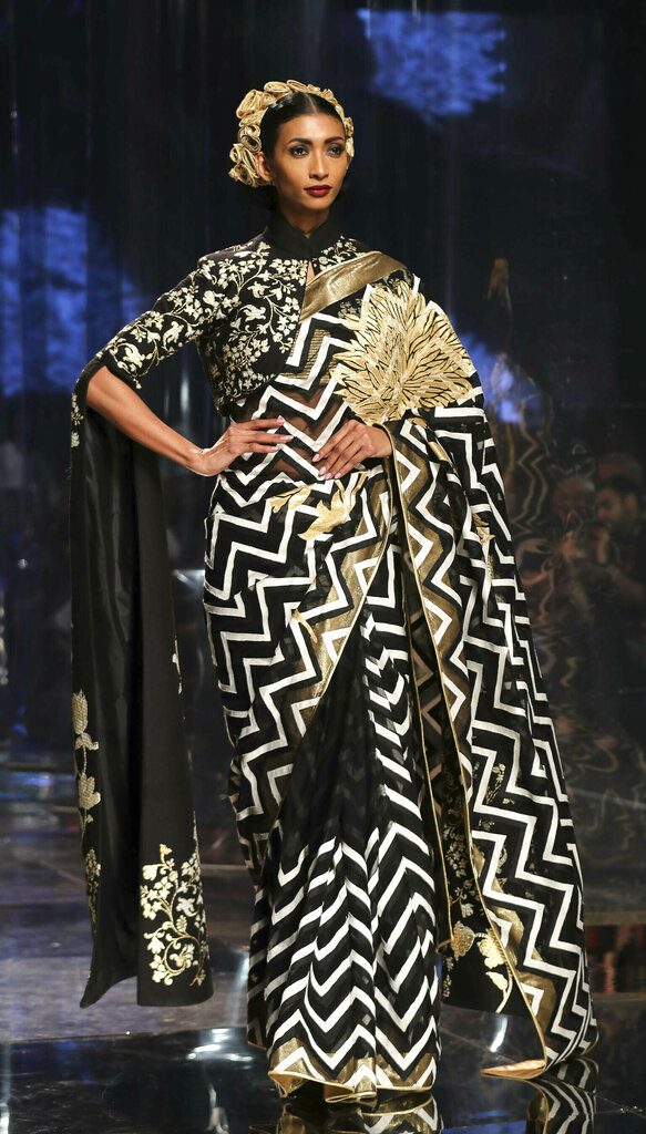 In this Saturday, March 16, 2019, photo, a model displays a creation of one of the top Indian designers celebrating the Sari, a traditional Indian attire, during the Grand finale of the Lotus make up India Fashion Week in New Delhi, India. It's fashion season in India's capital, with the country's top designers showcasing their latest collections to lure the rapidly growing domestic and export markets for Indian haute couture.(AP Photo/Manish Swarup)