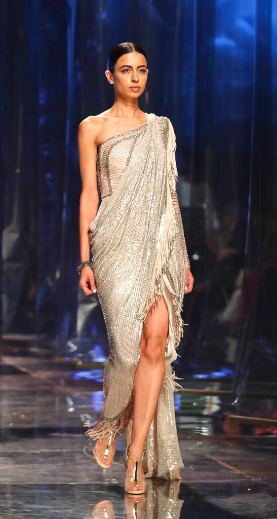 In this Saturday, March 16, 2019, photo, a model displays a creation of one of the top Indian designers celebrating the Sari, a traditional Indian attire, during the Grand finale of the Lotus make up India Fashion Week in New Delhi, India. It's fashion season in India's capital, with the country's top designers showcasing their latest collections to lure the rapidly growing domestic and export markets for Indian haute couture. (AP Photo/Manish Swarup)