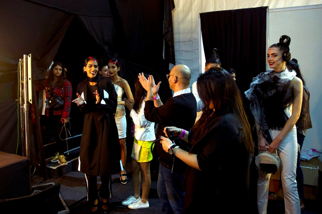 In this Thursday, March 14, 2019, photo, models, back stage managers and designers applaud at the end of a show during the Lotus Makeup India Fashion Week, in New Delhi, India. It's fashion season in India's capital city with the country's top designers showcasing their latest collections to lure the rapidly growing domestic and export markets for Indian haute couture. (AP Photo/Manish Swarup)