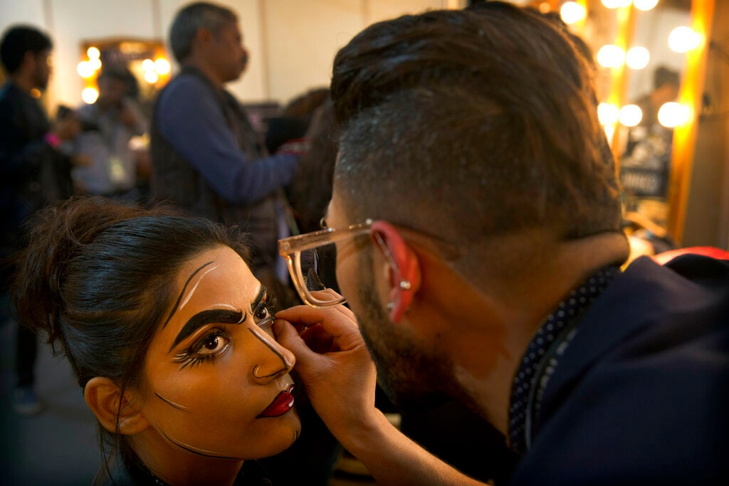 In this Thursday, March 14, 2019, photo, a makeup artist applies eyeliner to a model before a show during Lotus Makeup India Fashion Week, in New Delhi, India. It's fashion season in India's capital city with the country's top designers showcasing their latest collections to lure the rapidly growing domestic and export markets for Indian haute couture. (AP Photo/Manish Swarup)