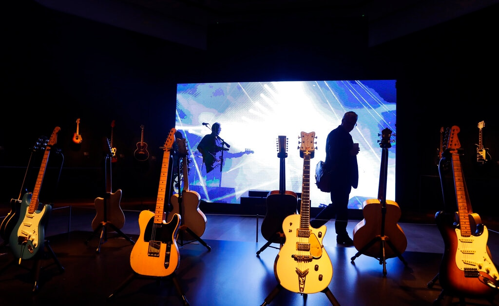A visitor walks past guitars from the collection of David Gilmour, guitarist, singer and songwriter of Pink Floyd, during a press opportunity at Christie's auction rooms in London on Wednesday, March 27, 2019. (AP Photo/Kirsty Wigglesworth)