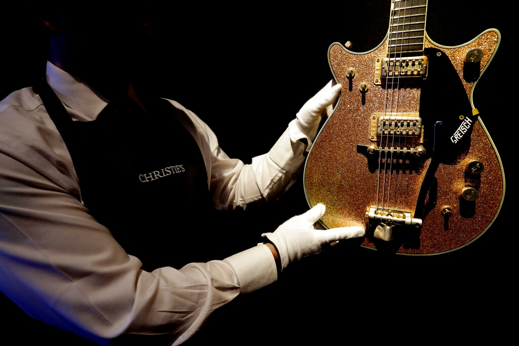 A technician displays a guitar estimated at $5,000-7,000, from the collection of David Gilmour, guitarist, singer and songwriter of Pink Floyd, during a press opportunity at Christie's auction rooms in London on Wednesday, March 27, 2019. (AP Photo/Kirsty Wigglesworth)