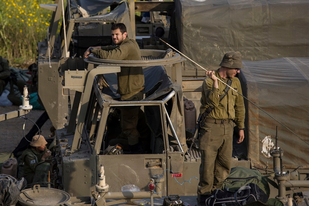 Israeli soldiers sit on top of mobile artillery near the border with Gaza. (AP Photo/Tsafrir Abayov)