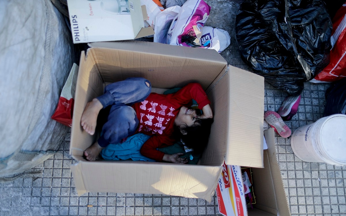Nicole Aleman lies inside a box on the street where she lives with her family in Buenos Aires, Argentina. A makeshift tent of cardboard and plastic bags on the side of a busy avenue in the Argentine capital serves as the shelter for the girl, her four siblings and her parents, who sleep sharing two old mattresses laid out on the concrete. (AP Photo/Natacha Pisarenko)