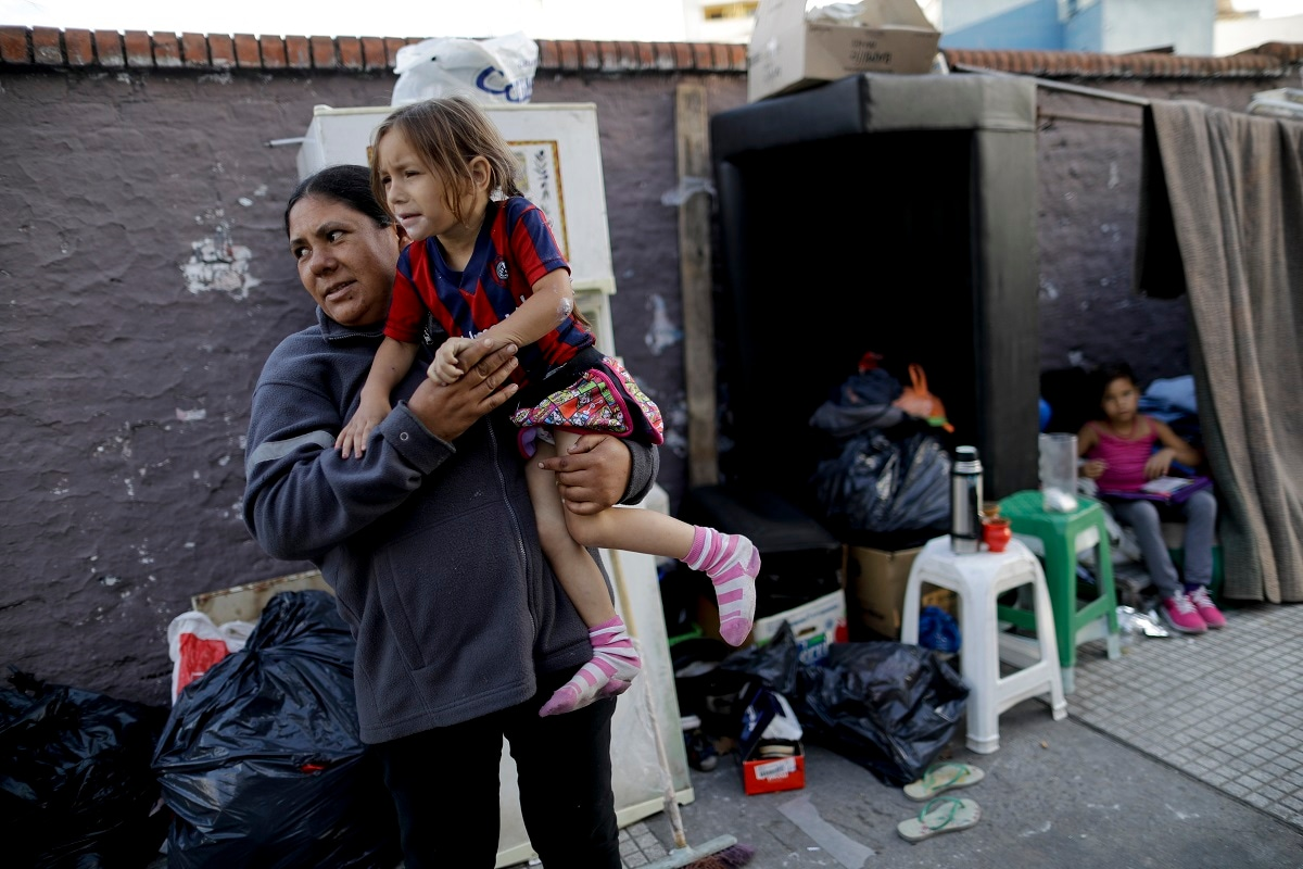 Damiana Aleman holds her daughter Valentina in front of their makeshift tent on a sidewalk in Buenos Aires, Argentina. Shelters in Buenos Aires are at full capacity. But since most are divided by gender, families usually prefer to stay on the streets rather than splitting up. (AP Photo/Natacha Pisarenko)