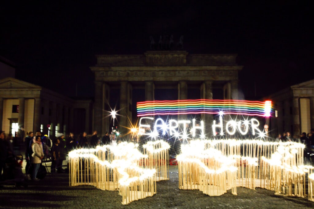 Activists of the World Wide Fund For Nature (WWF) write the words 'Earth Hour' with led-lights in front of the blacked out Brandenburg Gate to mark Earth Hour, in Berlin, Saturday, March 30, 2019. The global event Earth Hour is the symbolic switching off of the lights for one hour to help minimalize fossil fuel consumption as well as mitigate the effects of climate change. (AP Photo/Markus Schreiber)