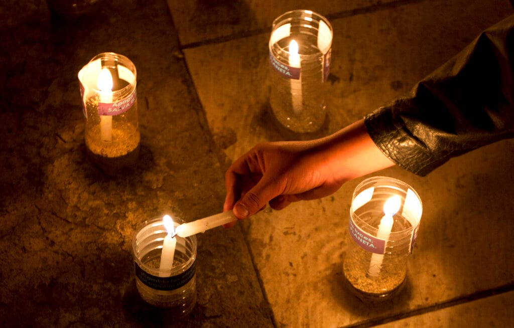 An activist lights a candle, that is part of a design that forms the number 60, to represent the minutes in an hour, during the Earth Hour celebrations, in La Paz, Bolivia, Saturday, March 30, 2019. (AP Photo/Juan Karita).