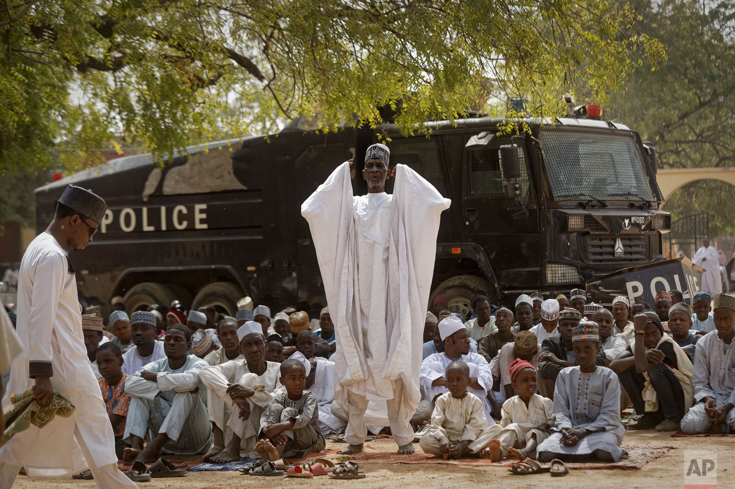 Muslims make traditional Friday prayers in front of a police riot truck, providing security due to the ongoing general threat of attacks by Islamic extremist group Boko Haram, at a mosque near to the Emir's palace in Kano, northern Nigeria Friday, February 15, 2019. Nigerians were preparing to go to the polls for a presidential election, one week after a surprise delay for Africa's largest democracy. (AP Photo/Ben Curtis)