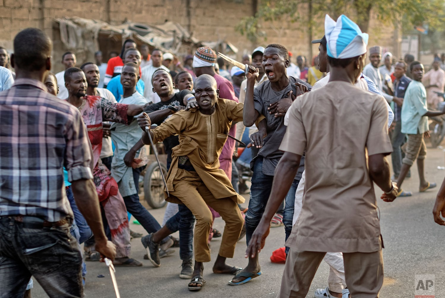 Supporters of the ruling party and main opposition party briefly pull knives and machetes on each other during an otherwise celebratory gathering of supporters of President Muhammadu Buhari anticipating victory, in Kano, northern Nigeria Monday, February 25, 2019. (AP Photo/Ben Curtis)