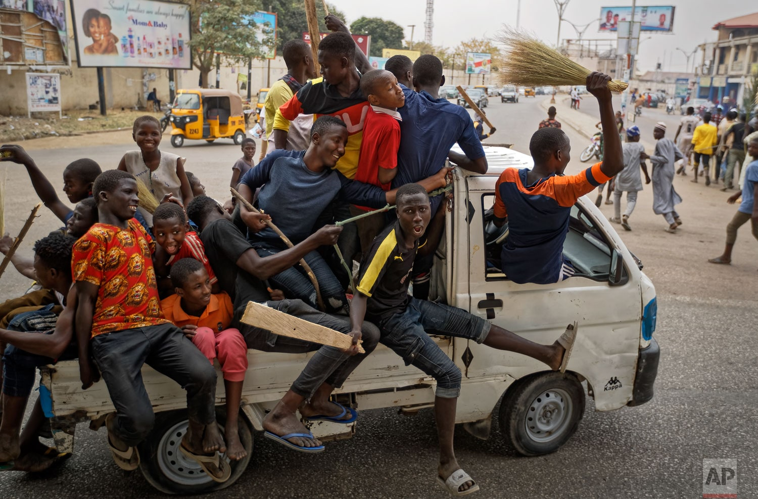 Supporters of Nigeria's President Muhammadu Buhari, some carrying crude weapons, ride on the back of a truck as they follow a march of others to celebrate his electoral win, on a street in Kano, northern Nigeria Wednesday, February 27, 2019. Buhari defended his sweeping win of a second term as free and fair and appealed to a