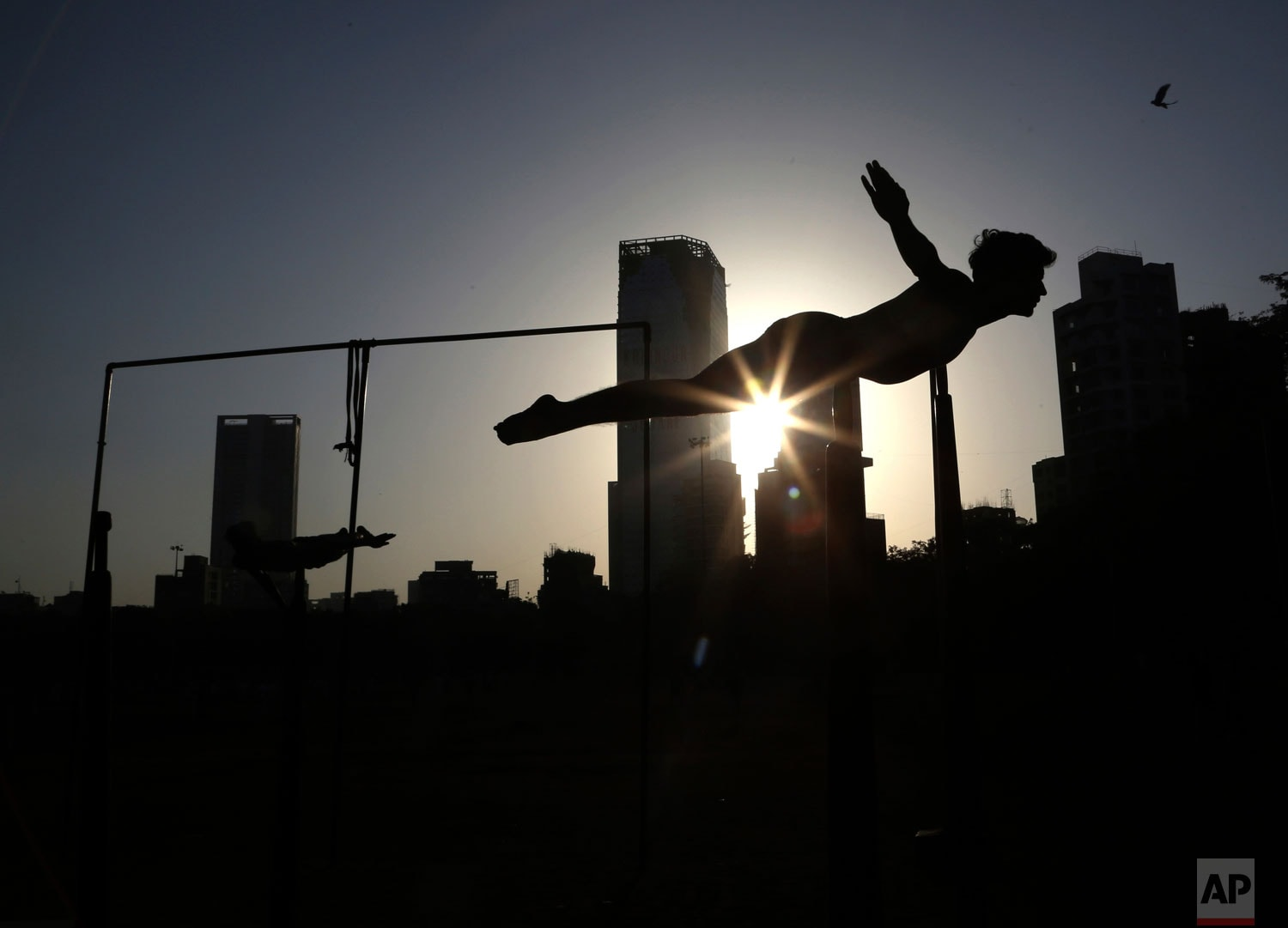 In this February 7, 2019, photo, a player performs on a Mallakhamb pole during an early morning training session at Shivaji Park in Mumbai, India. The word mallakhamb comes from malla, meaning wrestler, and khamb, or pole, and is a traditional training exercise for wrestlers in India. After centuries of being practised in isolation in the subcontinent, mallakhamb had its first international championship in Mumbai in February. (AP Photo/Rafiq Maqbool)