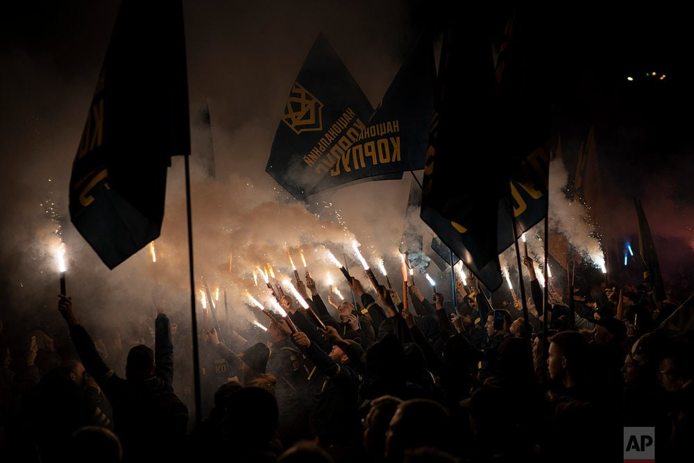Members of nationalist movements light flares during a rally marking Defender of Ukraine Day in Kiev, Ukraine. (AP Photo/Felipe Dana)