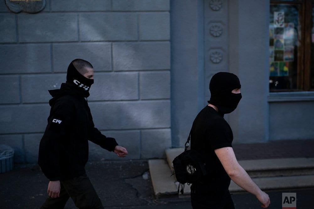 Members of the C14, some of them wearing balaclavas, march toward a Russian Orthodox church in Kiev, Ukraine. (AP Photo/Felipe Dana)