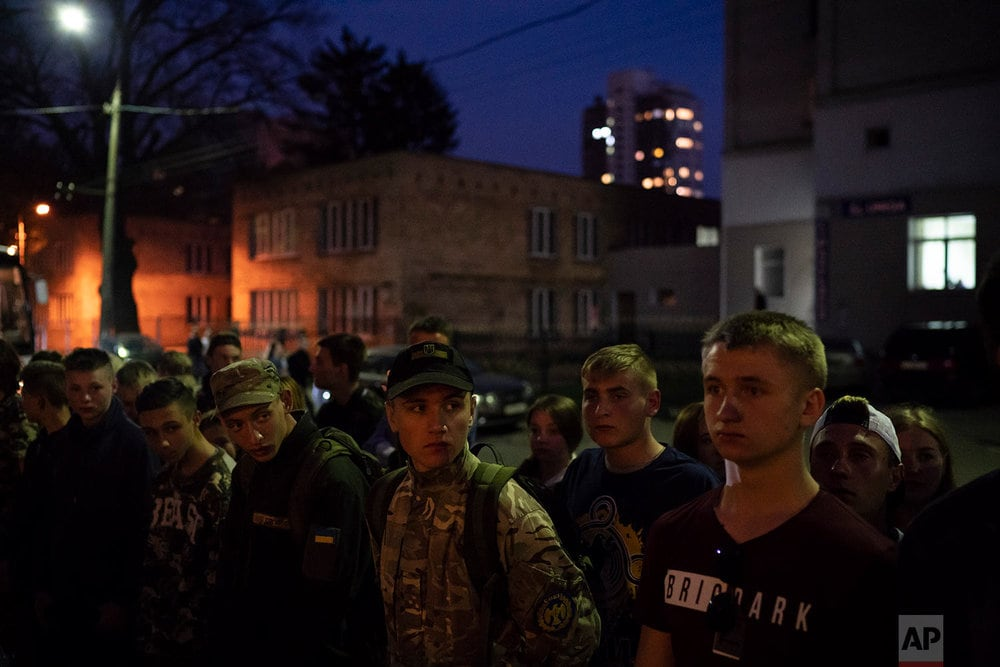Members of the nationalist group Sokil, the youth wing of the Svoboda party, stand in formation as they listen to instructions after a concert in Kiev, Ukraine. (AP Photo/Felipe Dana)