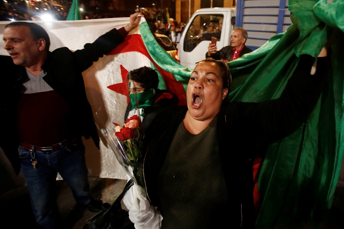 People carry a national flag as they celebrate on the streets. (REUTERS/Ramzi Boudina)