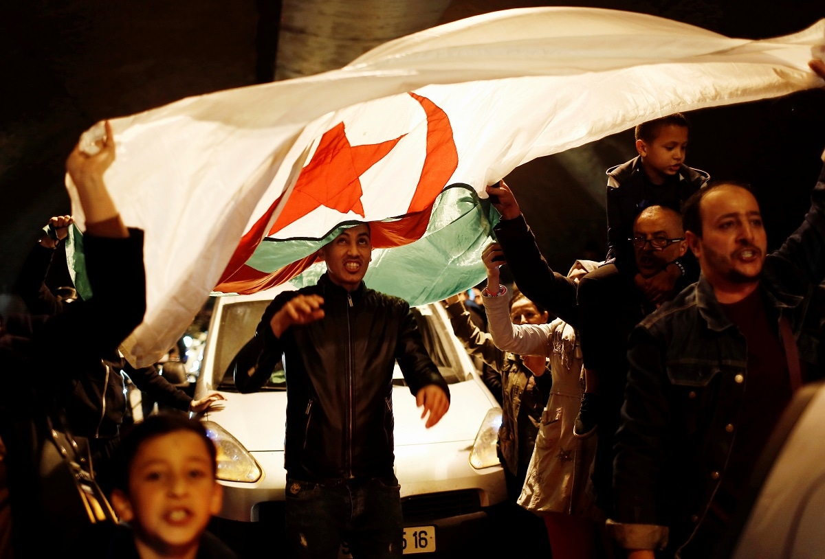 People carry a national flag as they celebrate on the streets after Algeria's President Abdelaziz Bouteflika submitted his resignation. (REUTERS/Ramzi Boudina)