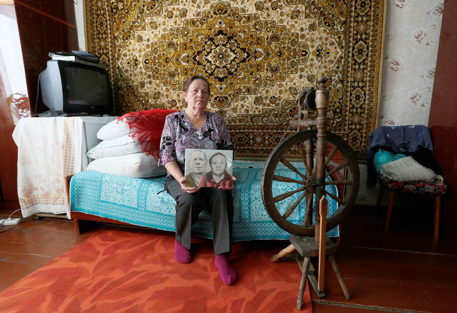 Lidia Slepets, 66, a resident of a Siberian settlement founded as a logging camp and part of the Soviet Union's Gulag prison labour system, shows a photograph of her parents while posing for a picture at her house in Tugach southeast of Krasnoyarsk, Russia October 30, 2018. The photograph shows Lidia's father, a former inmate of the Kraslag prison camp Gerasim Bersenyov (L), who married Anastasia Gaidaichuk (R), then a widow of a camp guard. REUTERS/Ilya Naymushin