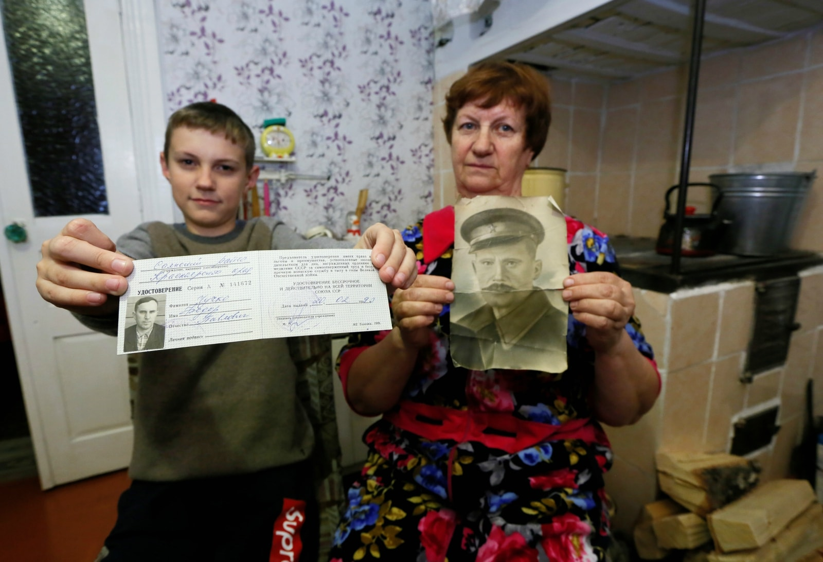 Local resident Vera Lazareva, 66, resident of a Siberian settlement founded as a logging camp and part of the Soviet Union's Gulag prison labour system, and her grandson Grigory, 13, show photographs of their late relatives while posing for a picture at a house in Tugach southeast of Krasnoyarsk, Russia October 29, 2018. The photographs show guard of Kraslag prison camp Pavel Yarg (R) and inmate Fyodor Chuchko. REUTERS/Ilya Naymushin